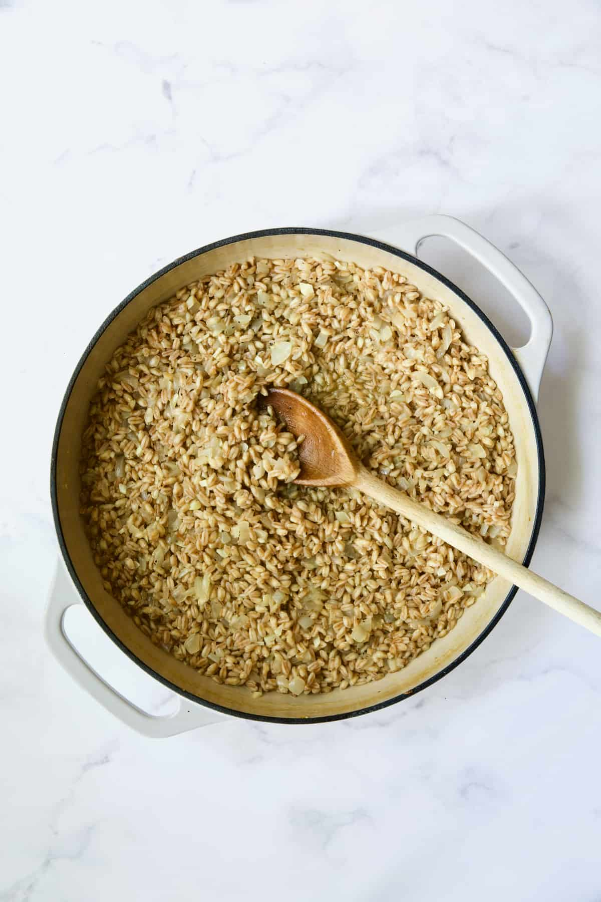 Process photo of farro risotto after broth is absorbed being stirred with wooden spoon.