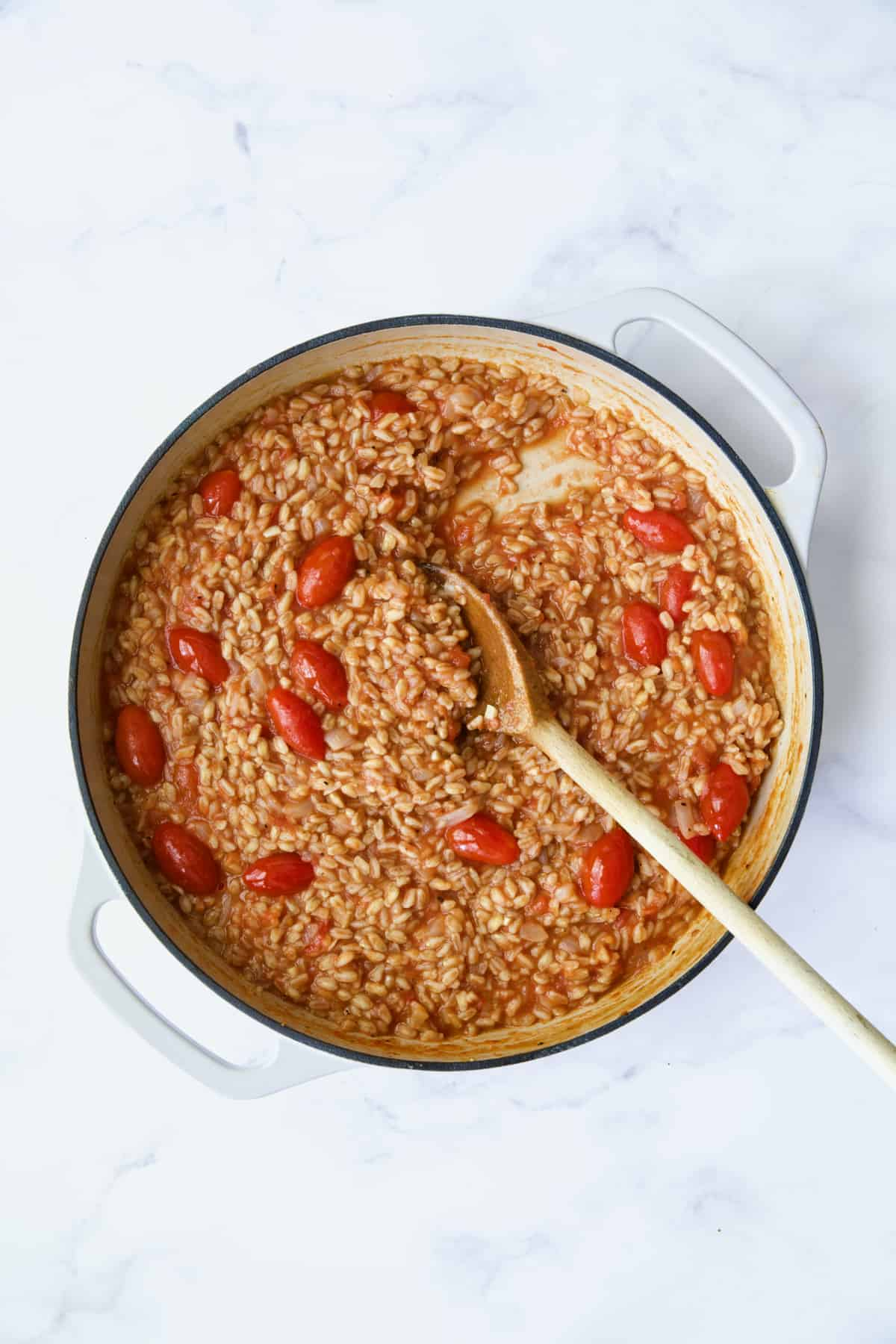 Process photo of farro risotto after crushed tomatoes are added being stirred with wooden spoon.