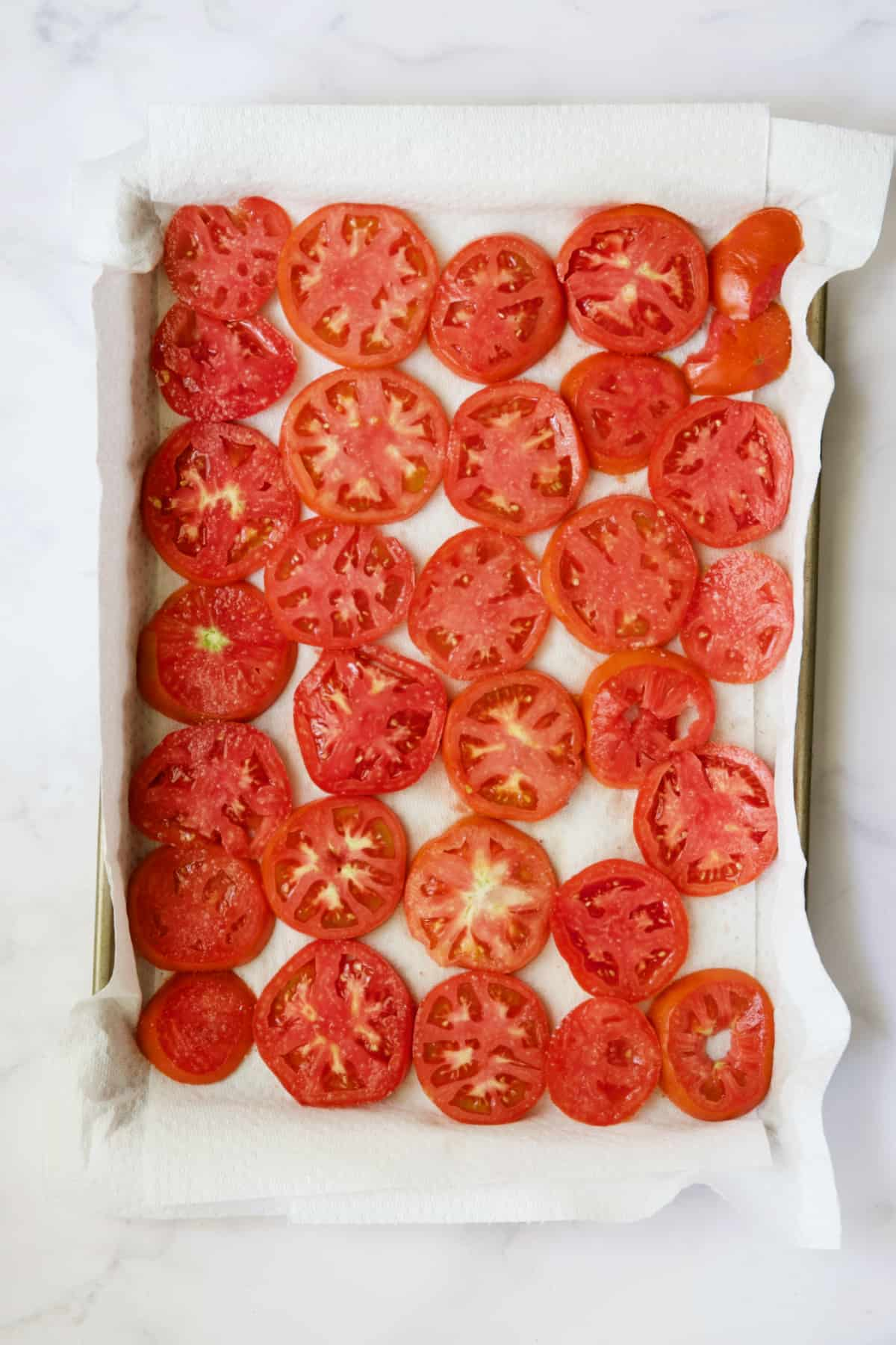Tomato slices on paper towel-lined baking sheet.