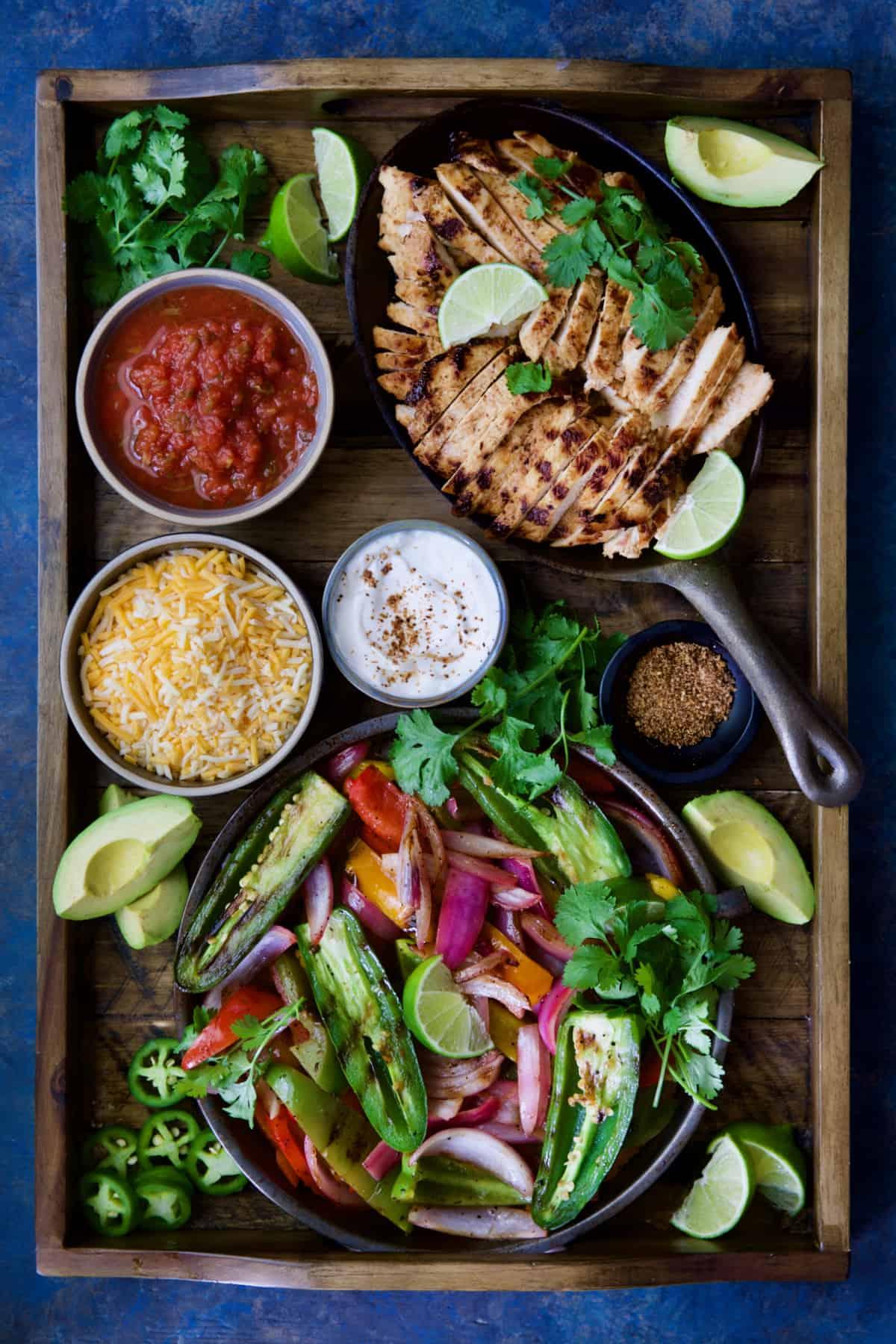 Grilled Tajin-Seasoned Chicken Fajitas on wood tray with accompaniments:  Salsa, sour cream, cheese, etc.