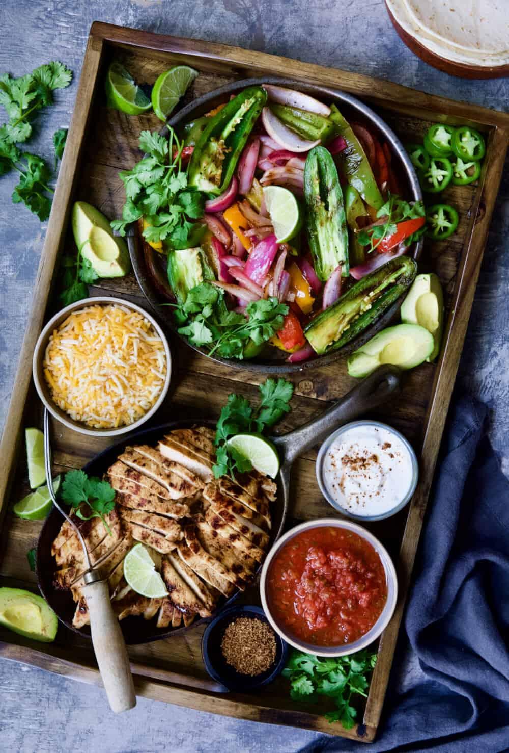 Grilled Tajin-Seasoned Chicken Fajitas on wood board with all the accompaniments.