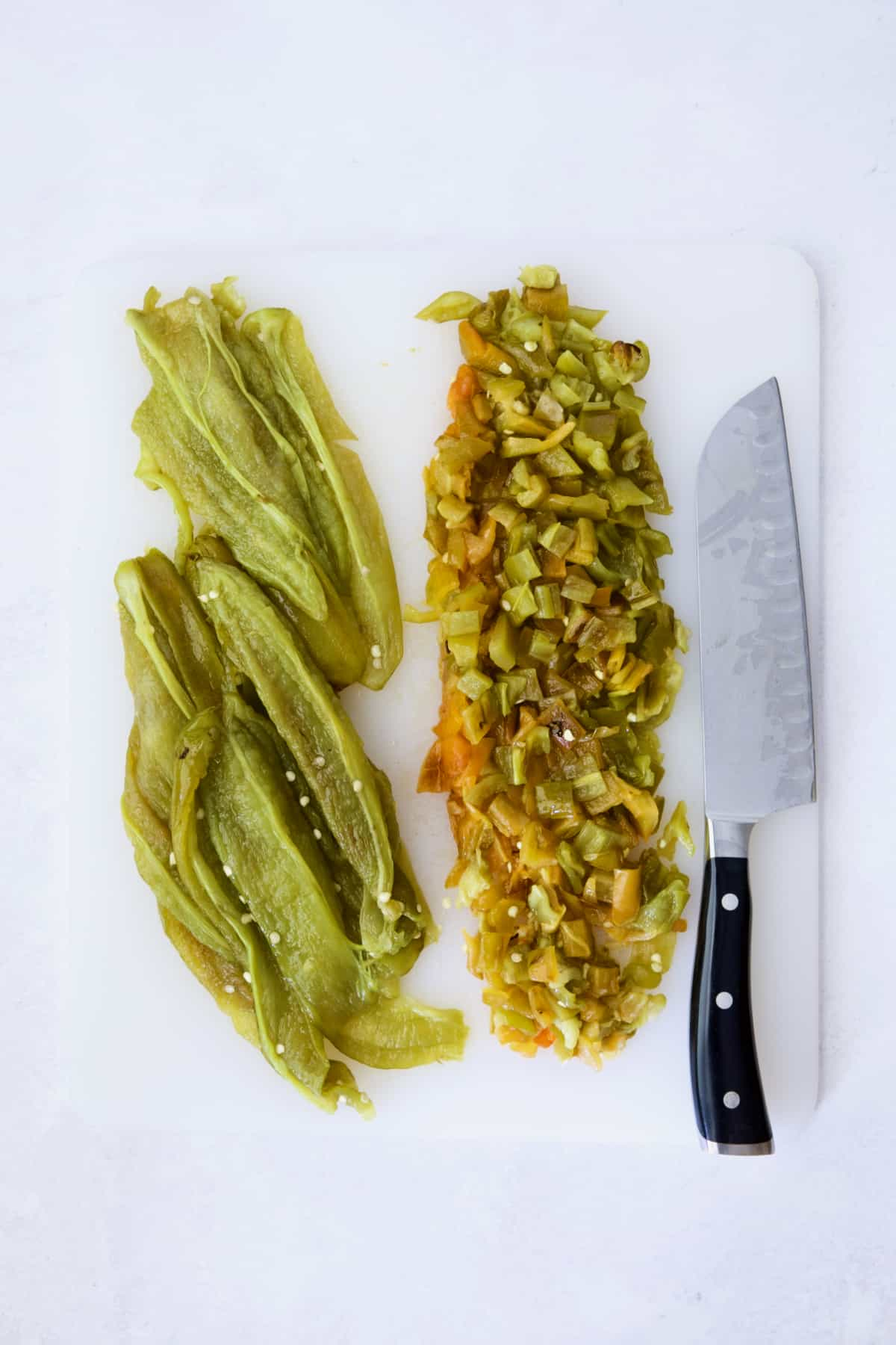 Seeded and roasted Hatch green chiles with half diced on white cutting board.