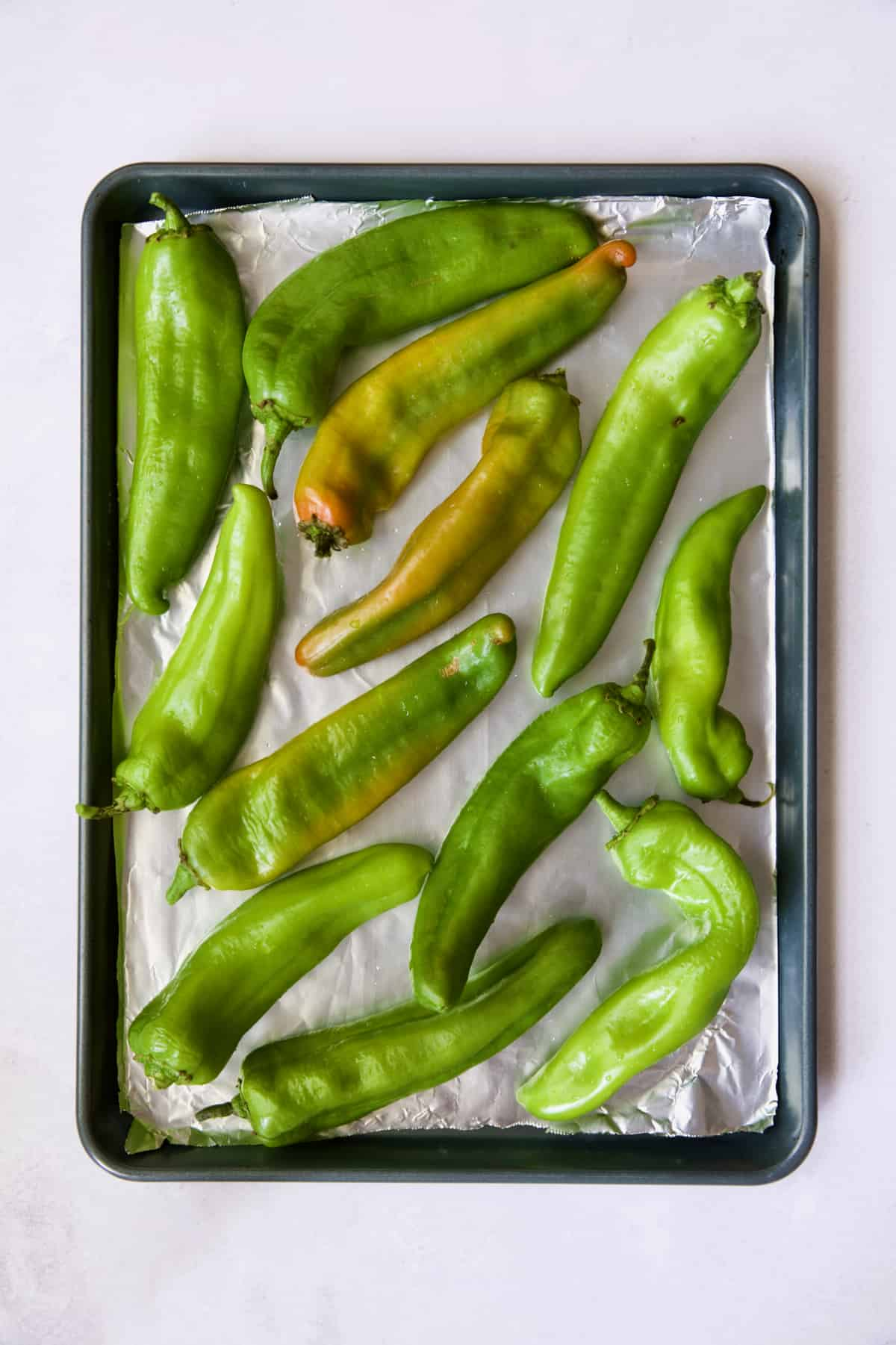 Hatch green chiles on rimmed sheet pan before being roasted.