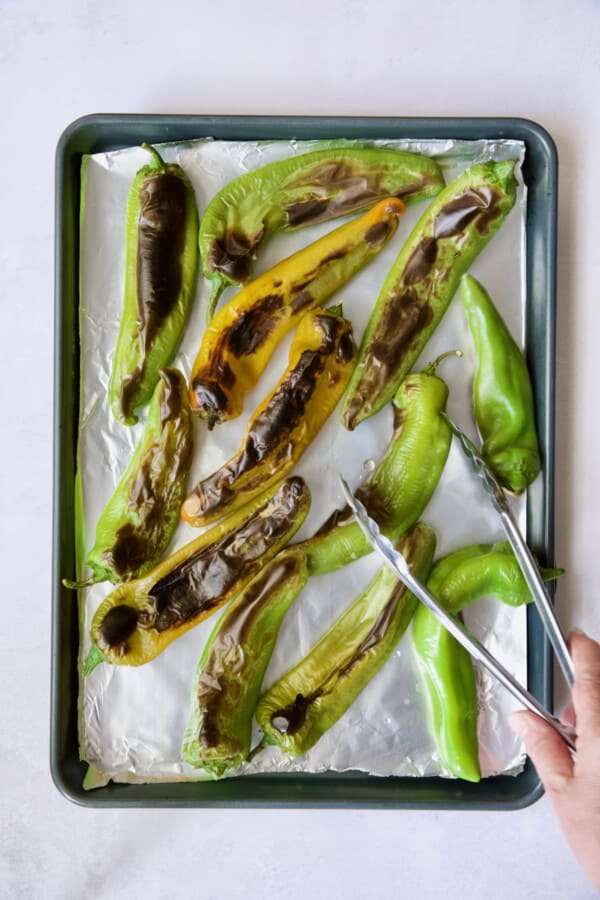 Half roasted Hatch green chiles being turned with tongs.