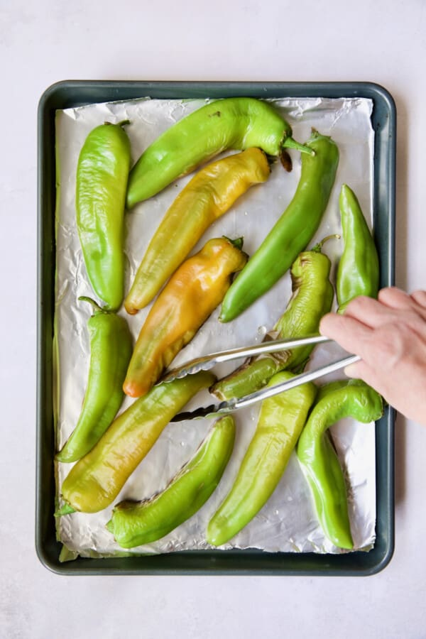 Hatch green chiles on rimmed sheet pan being turned with tongs.