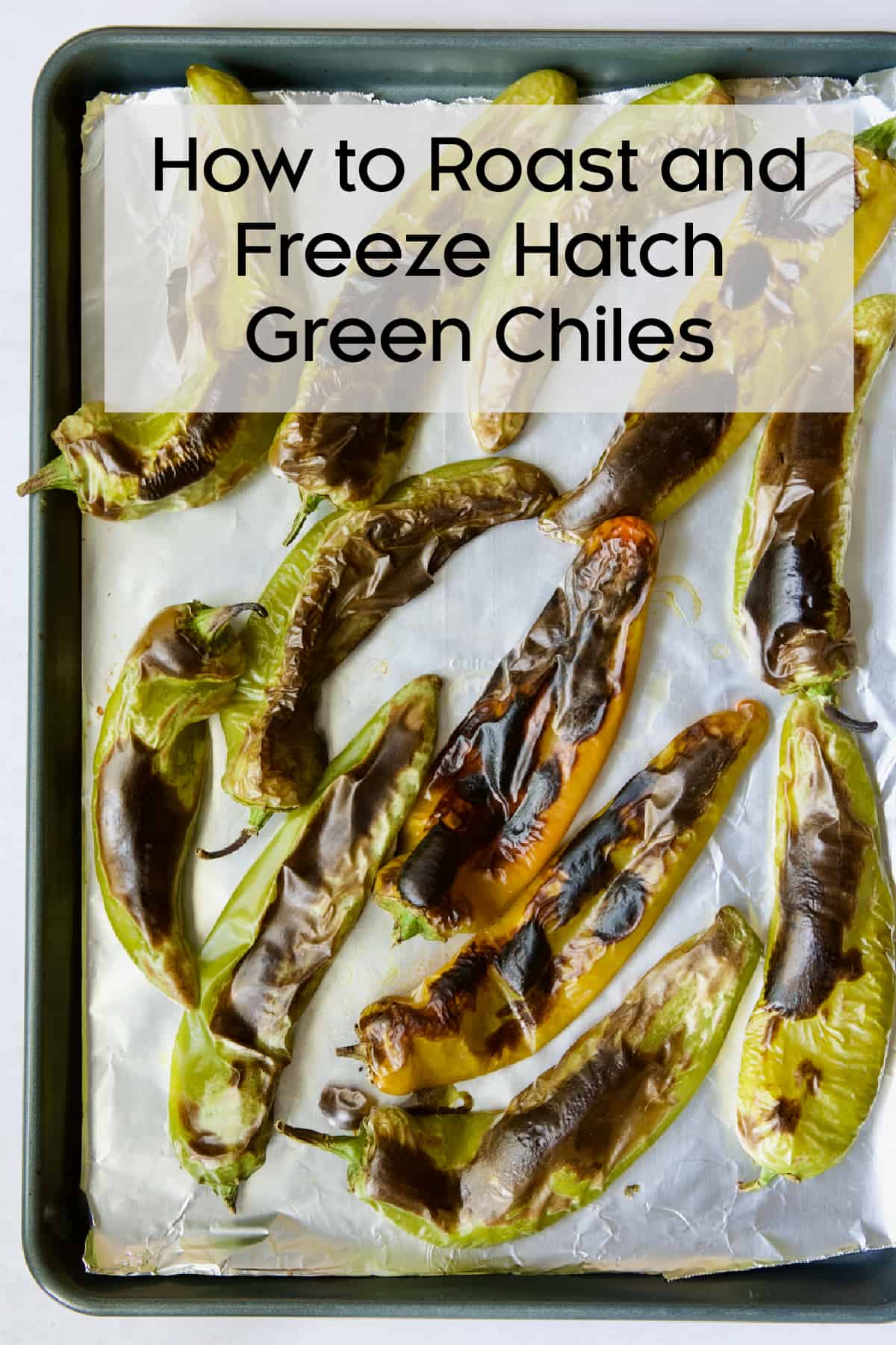 Hatch green chiles on aluminum-foil lined sheet pan with title of post.