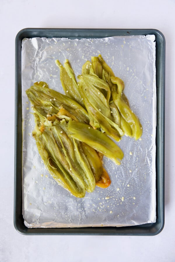 Pile of roasted and seeded Hatch green chiles on rimmed sheet pan.