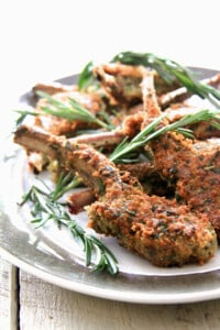 Parmesan and Herb-Crusted Lamb Chops on platter garnished with rosemary sprigs.