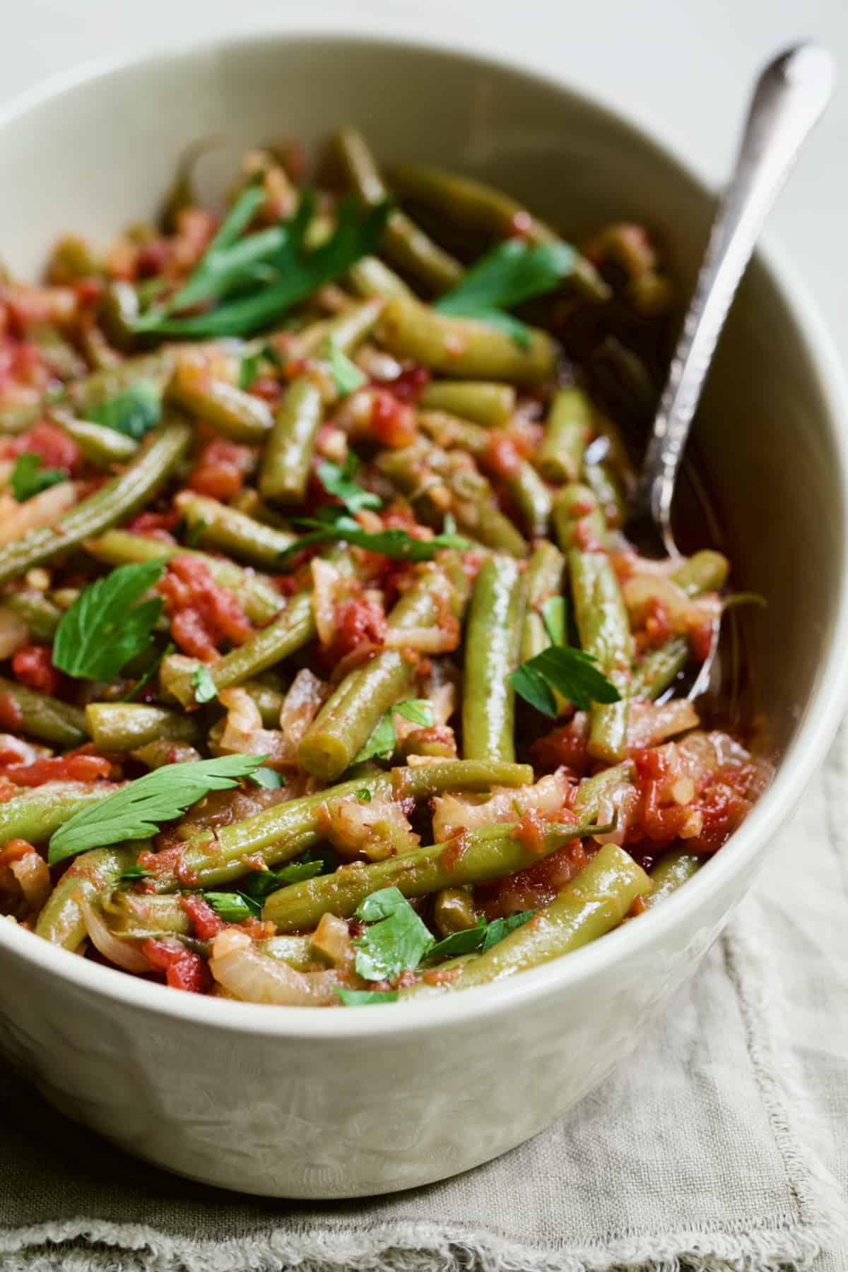 Mediterranean Braised Green Beans with Tomatoes in serving dish with serving spoon on beige fringed napkin.