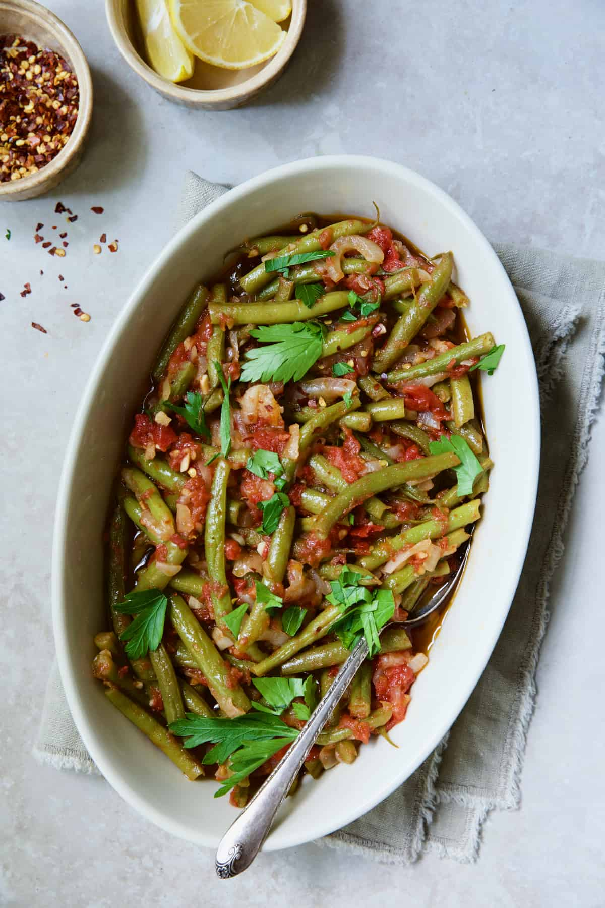 Mediterranean Braised Green Beans with Tomatoes in oval serving dish garnished with fresh parsley.