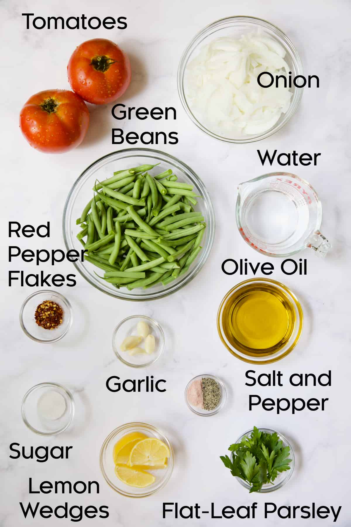 Ingredients for Mediterranean Braised Green Beans with Tomatoes in glass bowls.