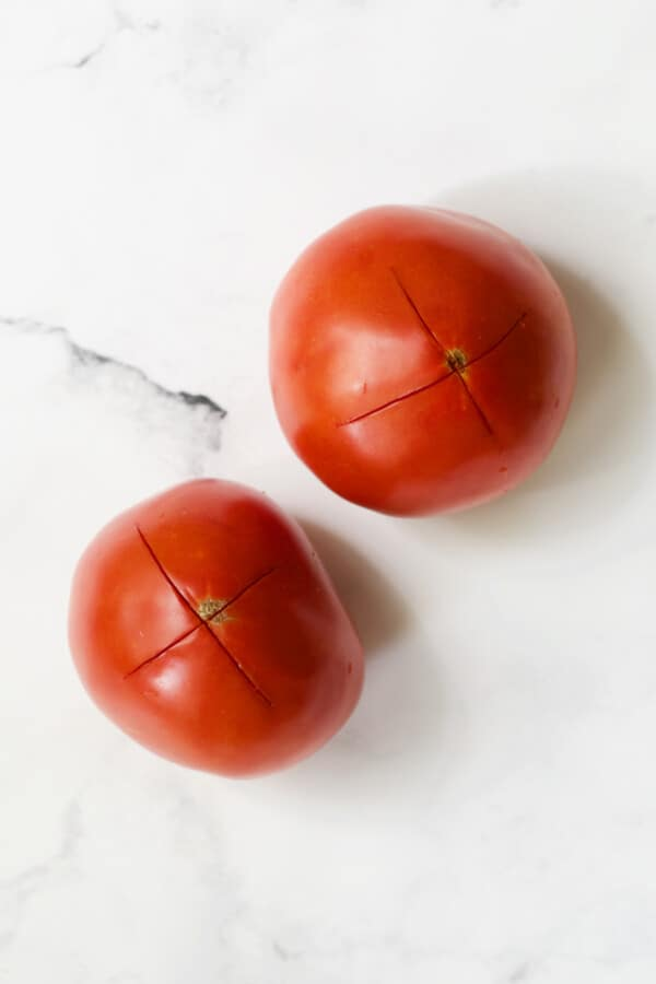 Two tomatoes on white background that have an X scored in the bottom.