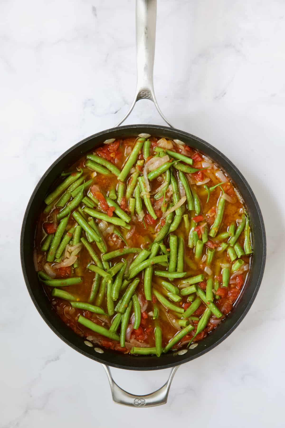 Green beans and tomatoes cooking in skillet right after fresh green beans are added.