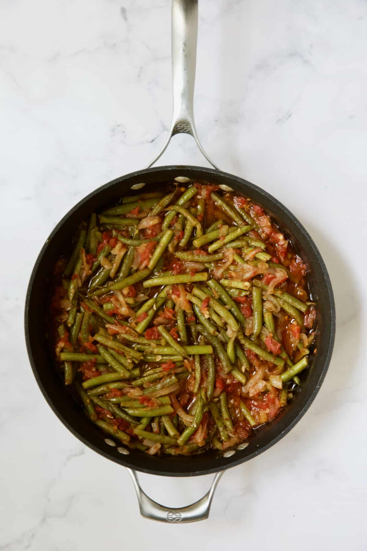 Cooked green beans and tomatoes in skillet.