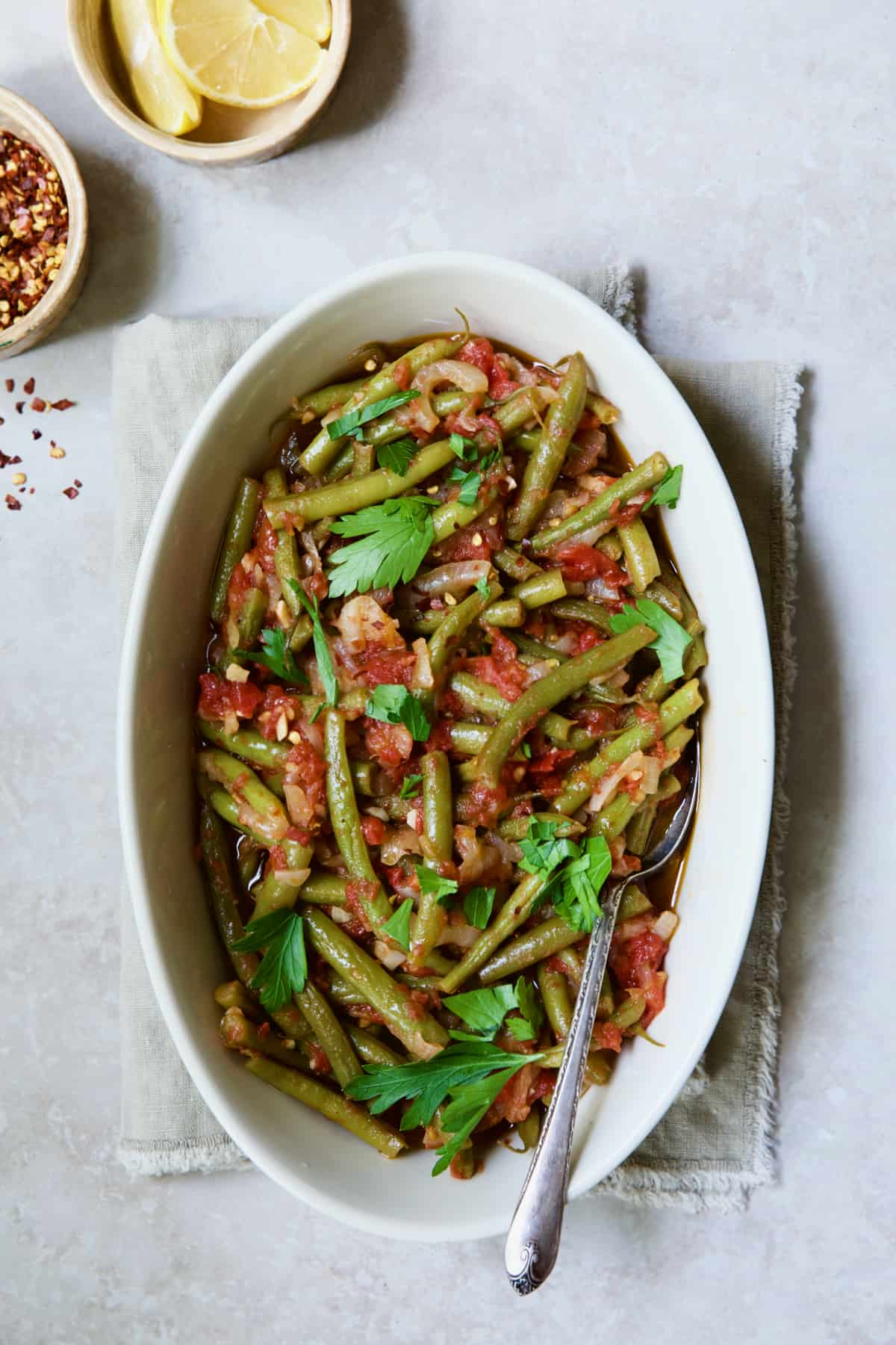 Mediterranean Braised Green Beans with Tomatoes in oval serving dish with serving spoon garnished with fresh parsley.