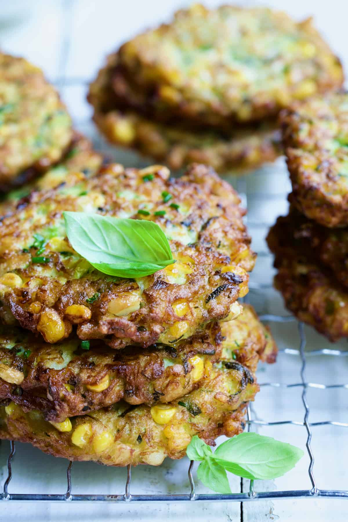Stack of three Zucchini Corn Cakes with more in the background.