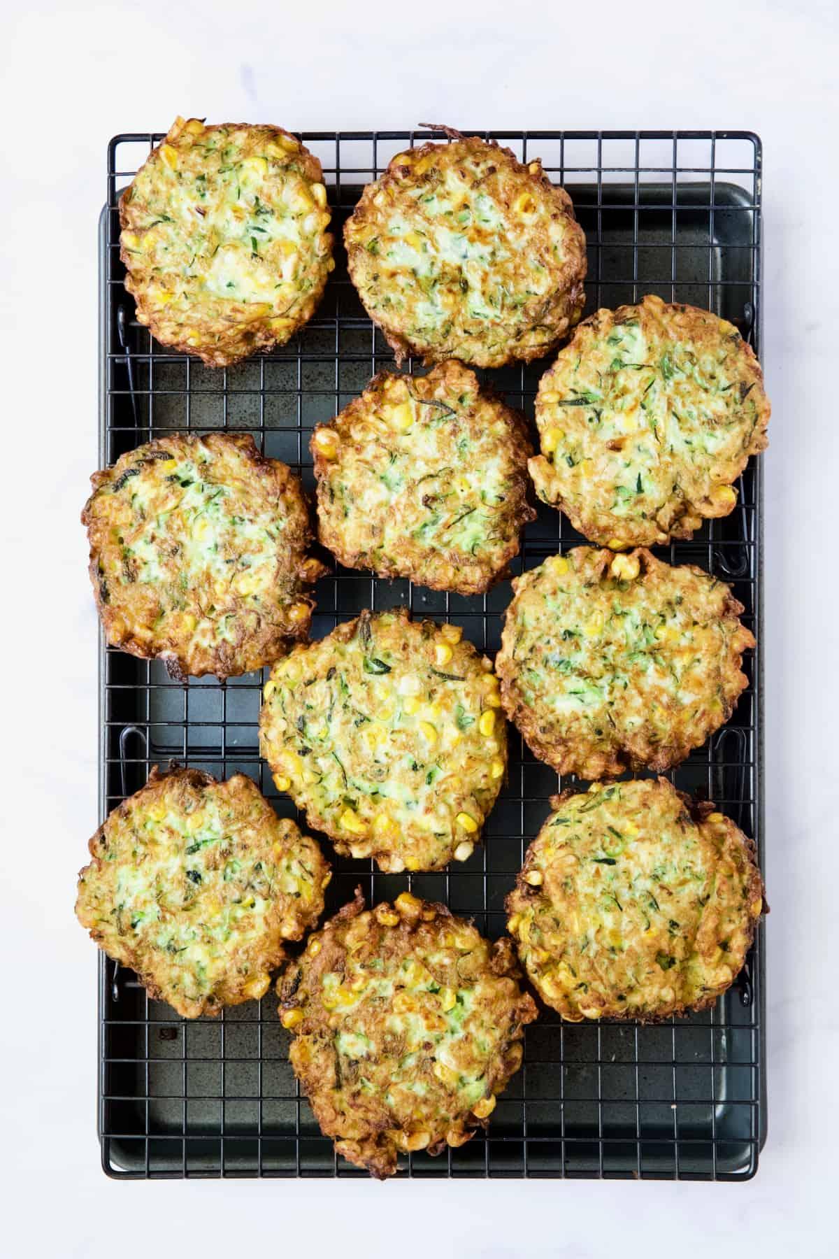Ten Zucchini Corn Fritters on rack set over baking sheet.