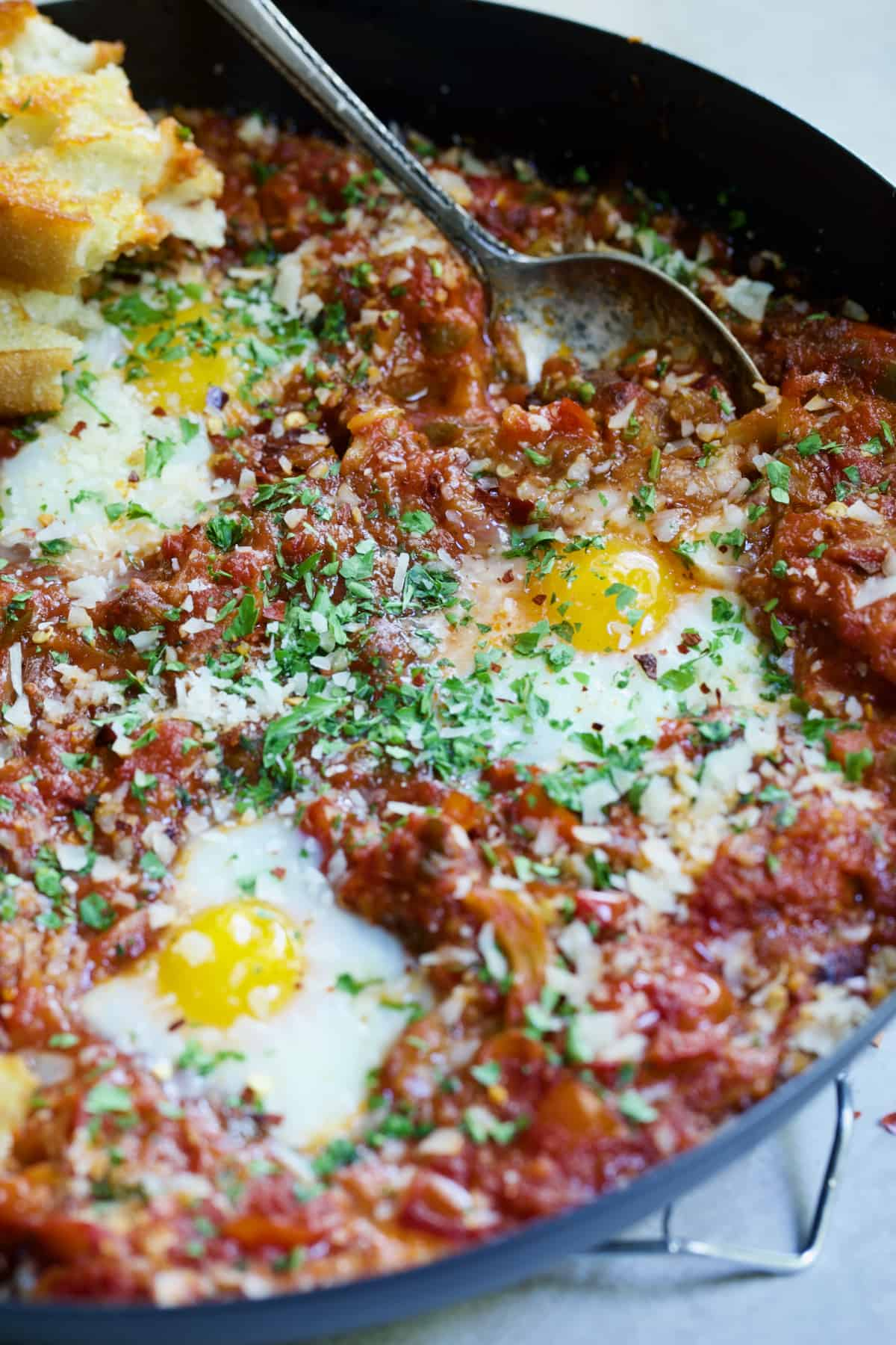 Eggs in Purgatory with Italian Sausage with serving spoon in black skillet.