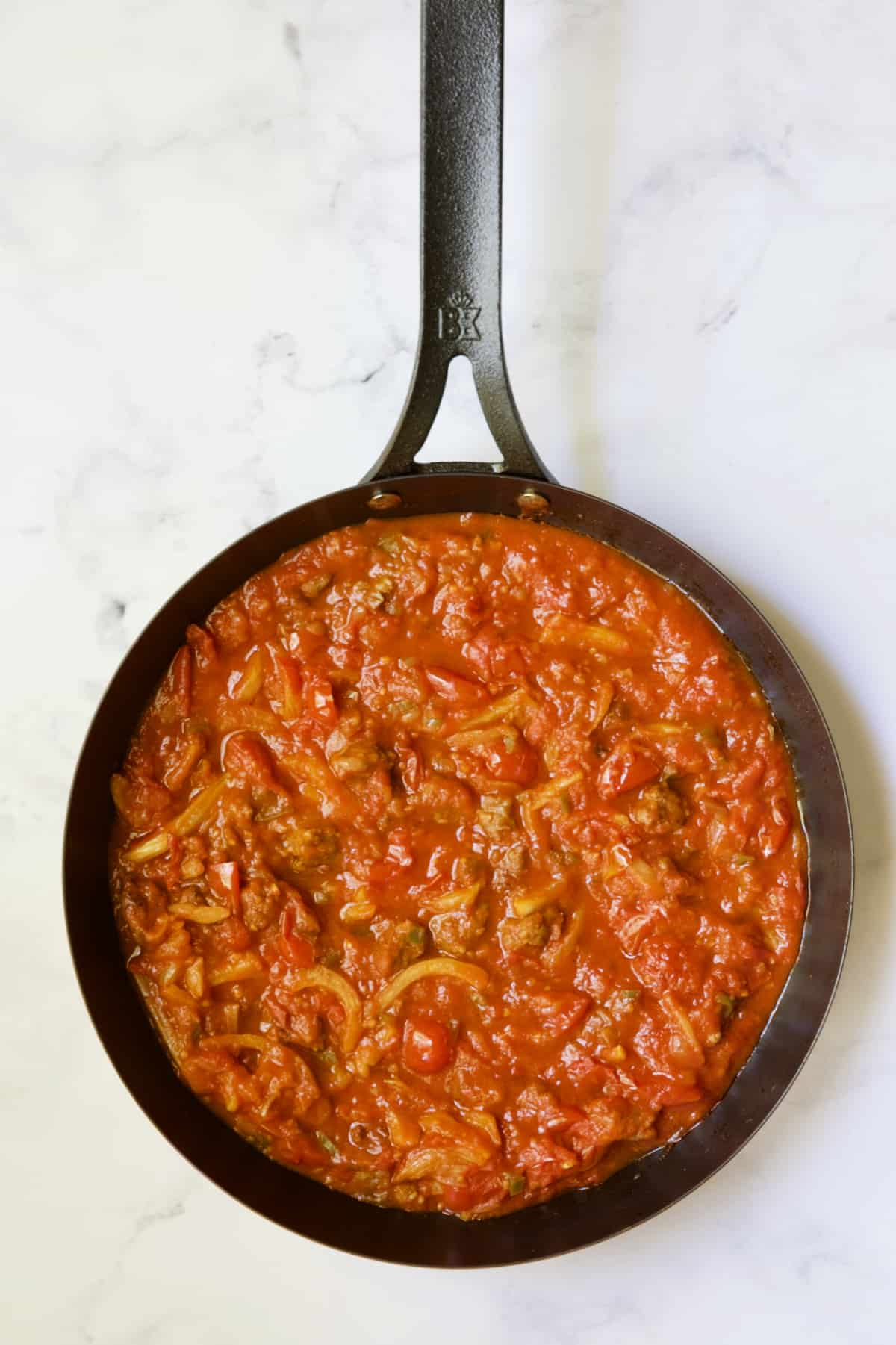 Tomato sauce with sausage in black skillet.