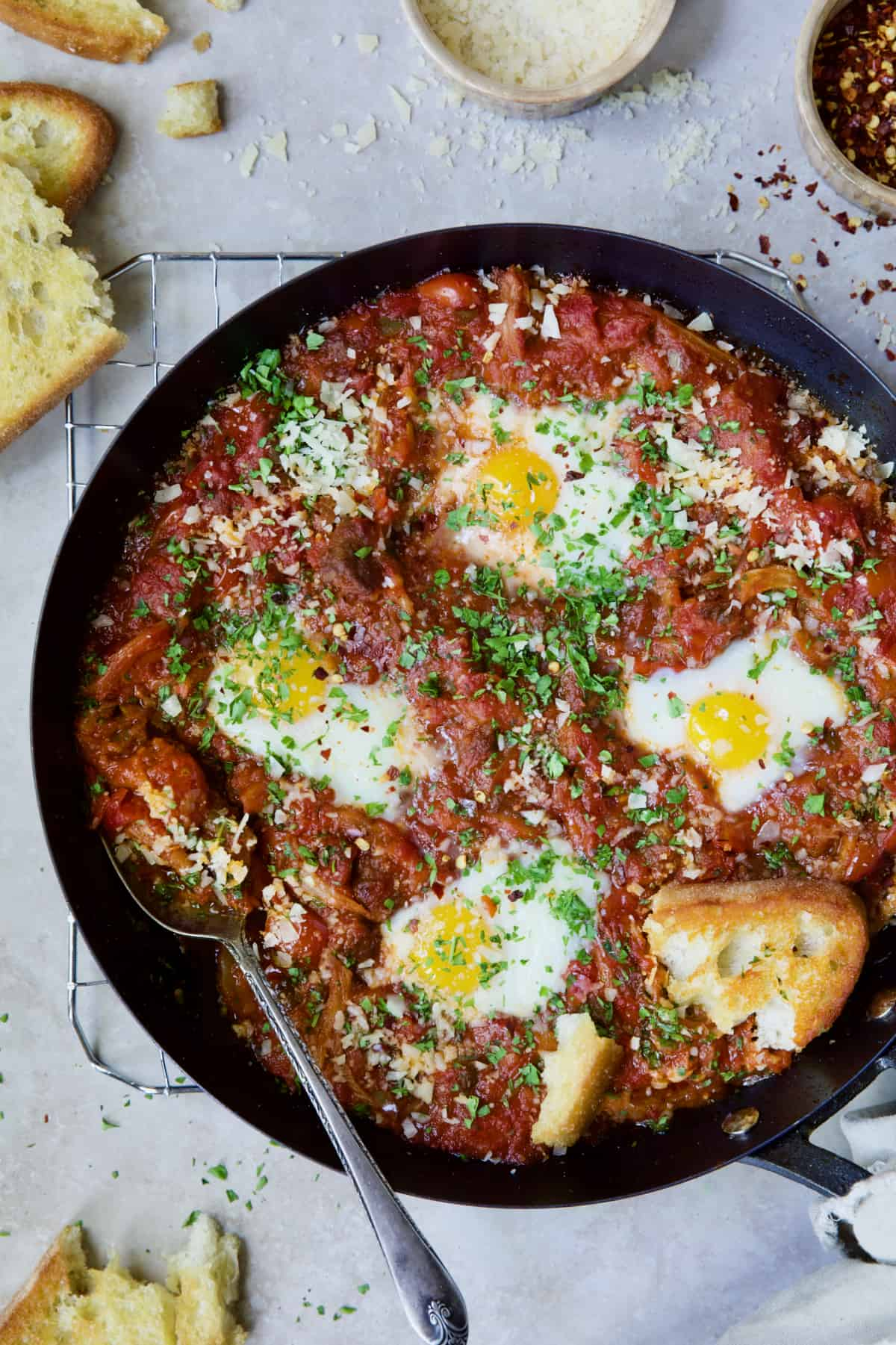 Eggs in Purgatory with Italian Sausage in skillet with serving spoon.