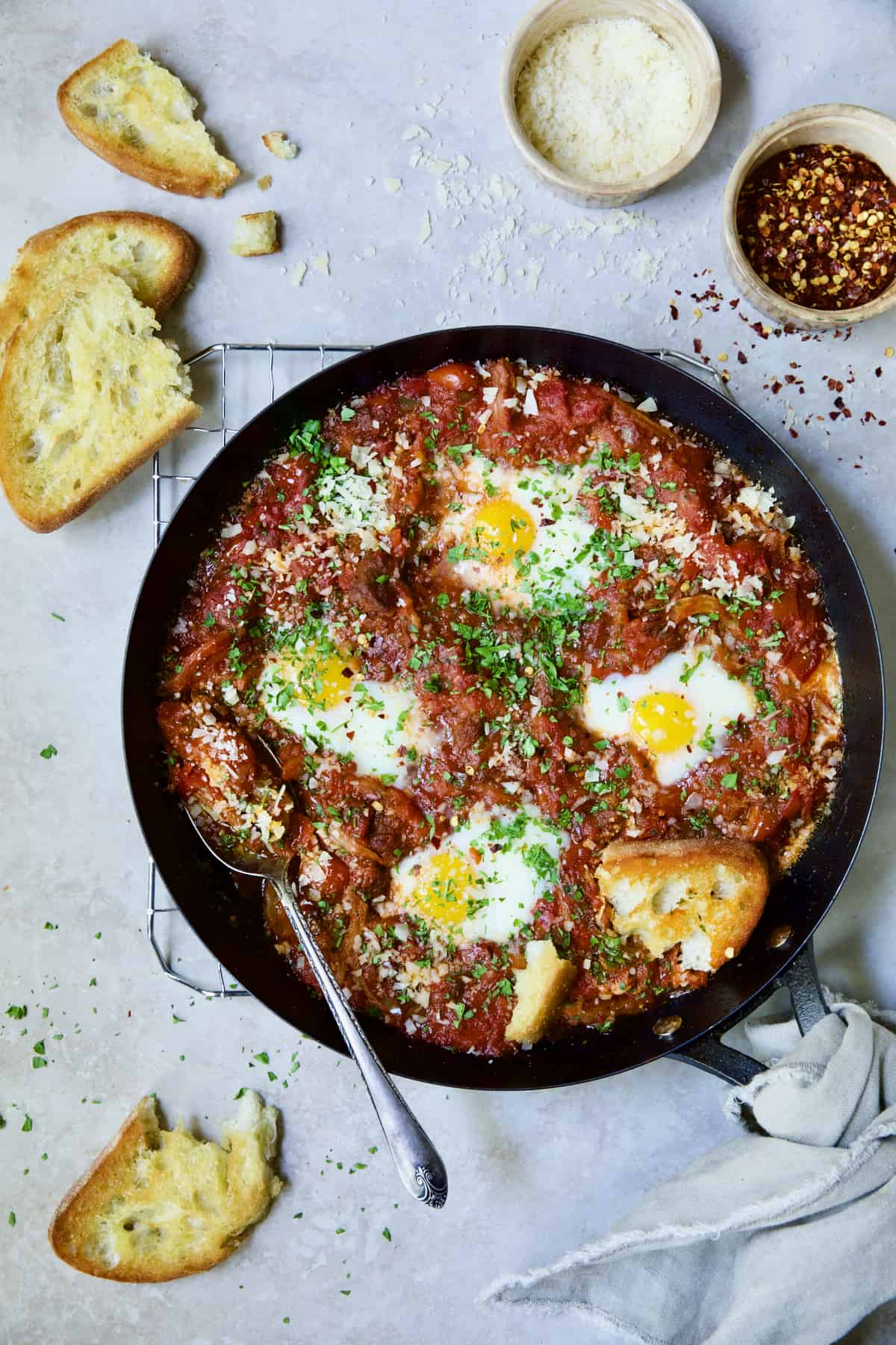 Eggs in Purgatory with Italian Sausage in skillet with broken toasted bread.