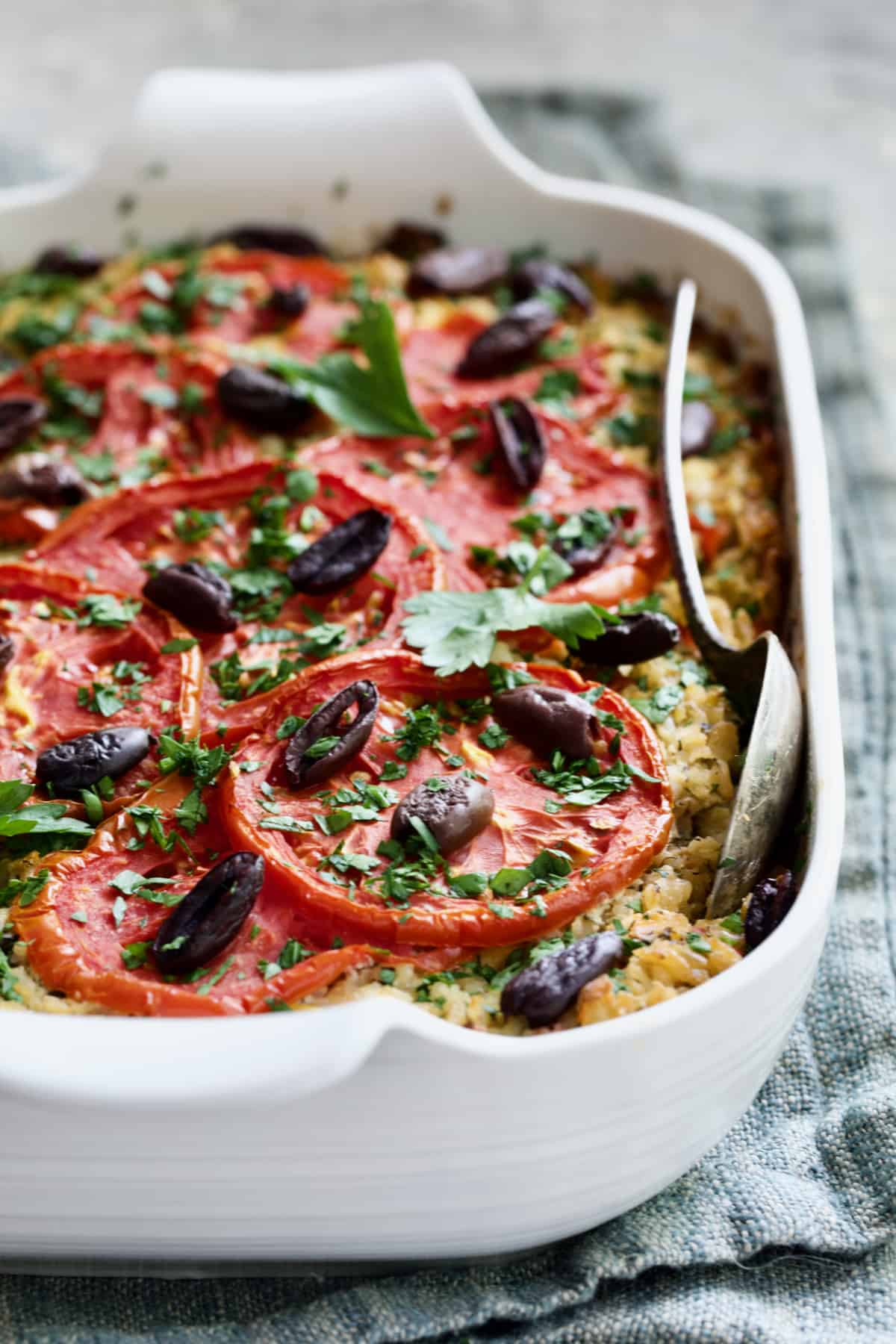 Greek Brown Rice and Vegetable Casserole in white baking dish with serving spoon on blue napkin.