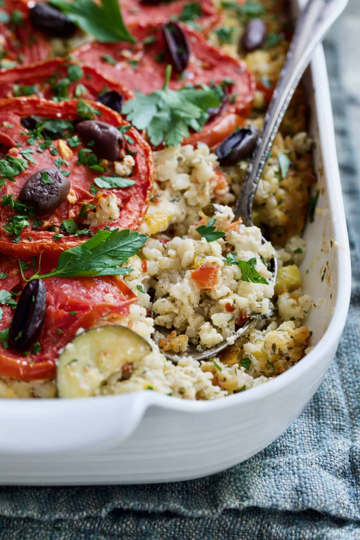Greek Brown Rice and Vegetable Casserole being scooped up from baking dish with spoon.