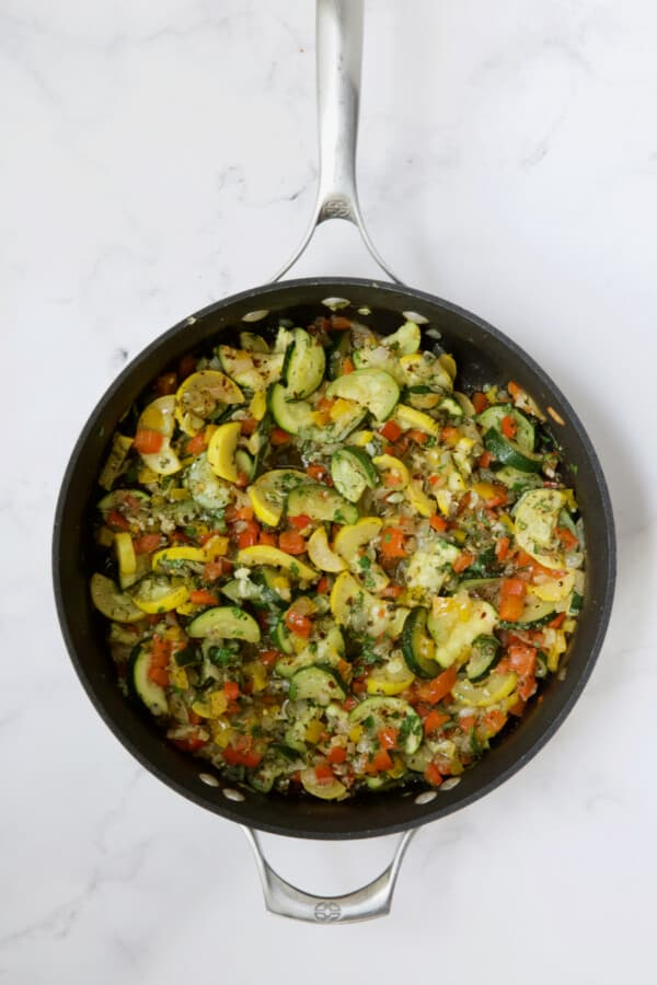 Cooked onions, peppers, zucchini and yellow squash in skillet.