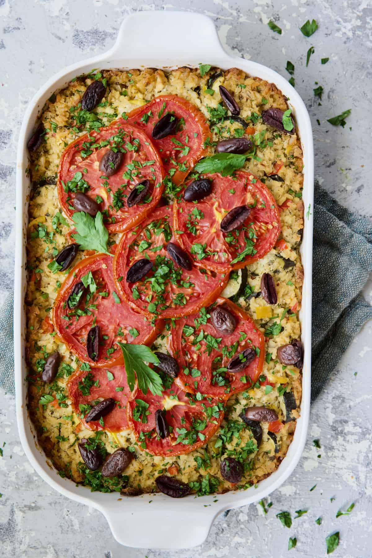 Greek Brown Rice and Vegetable Casserole in white baking dish garnished with fresh parsley.