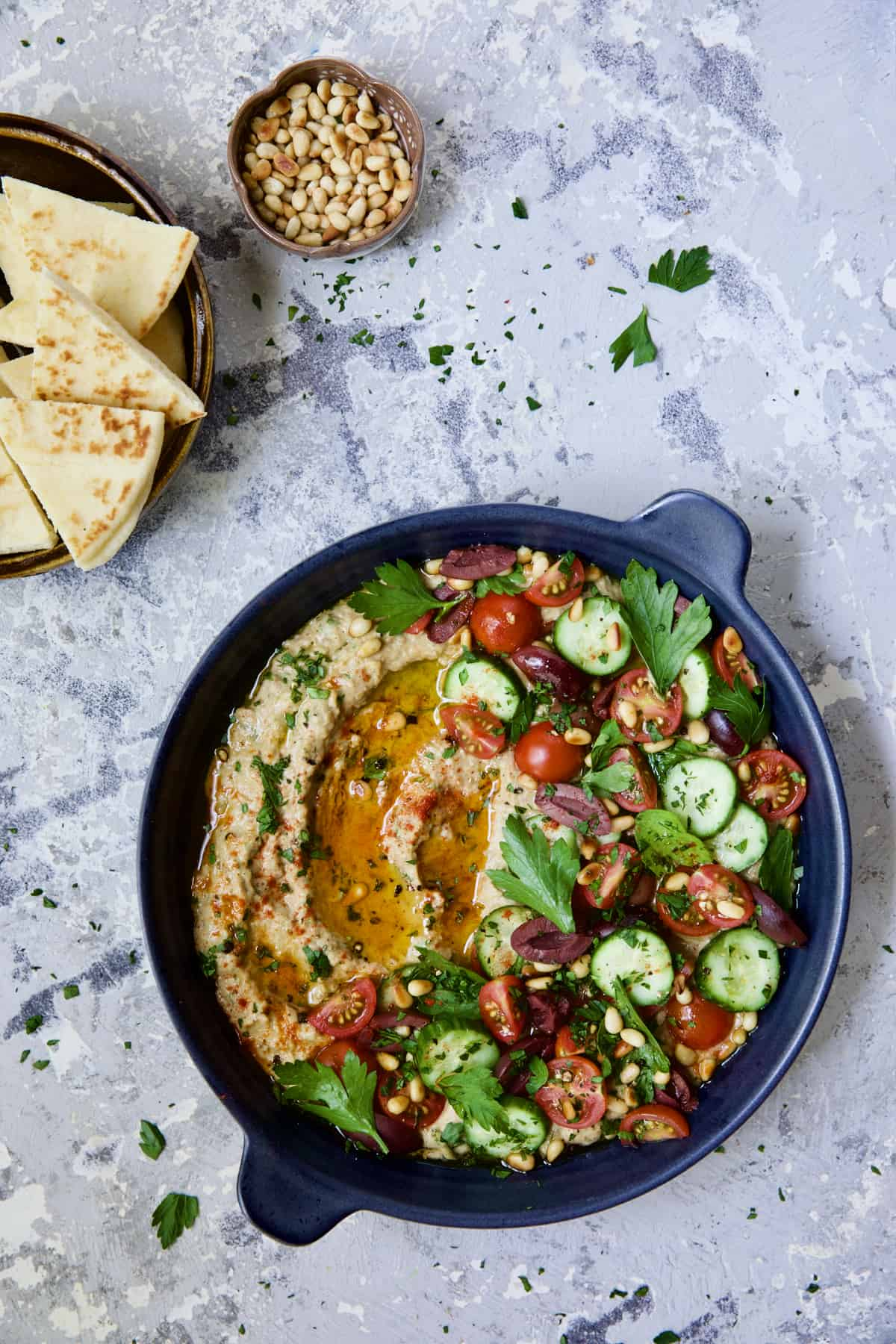 Loaded Roasted Eggplant Dip (Baba Ganoush) in blue dish on distressed background with pita chips and pine nuts.
