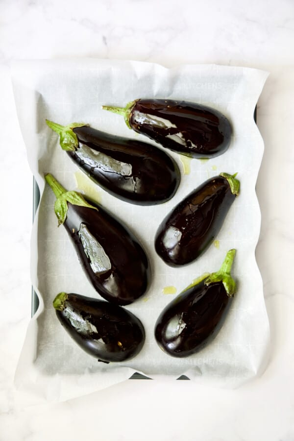 Six eggplant halves on parchment paper-lined baking sheet before being roasted.