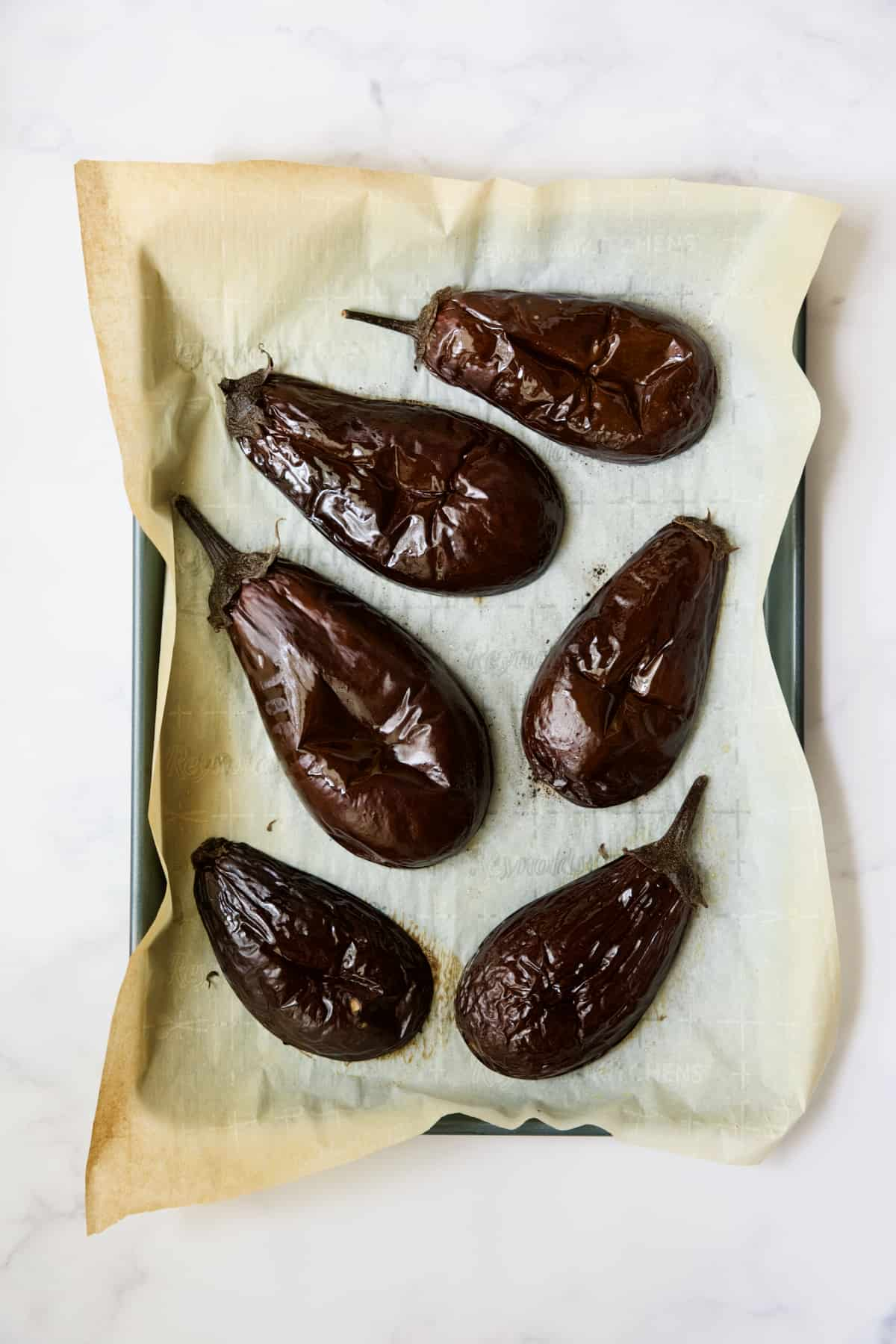 Six roasted eggplant halves on parchment paper-lined baking sheet.