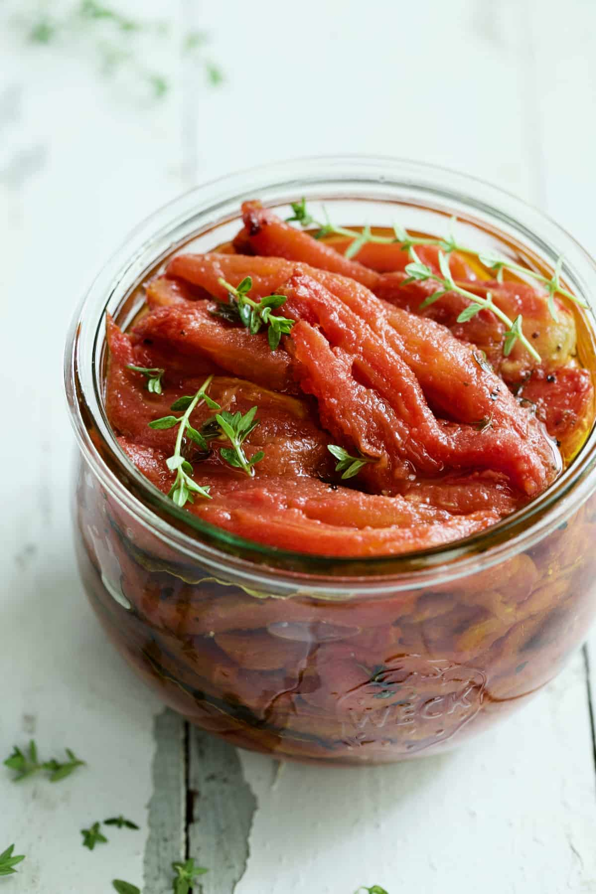 Tomato Confit in glass jar garnished with fresh thyme sprigs on white distressed background.