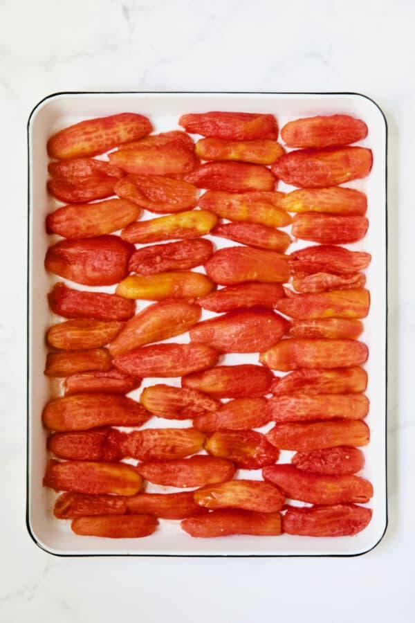 40 plum tomato halves on white enameled baking sheet.