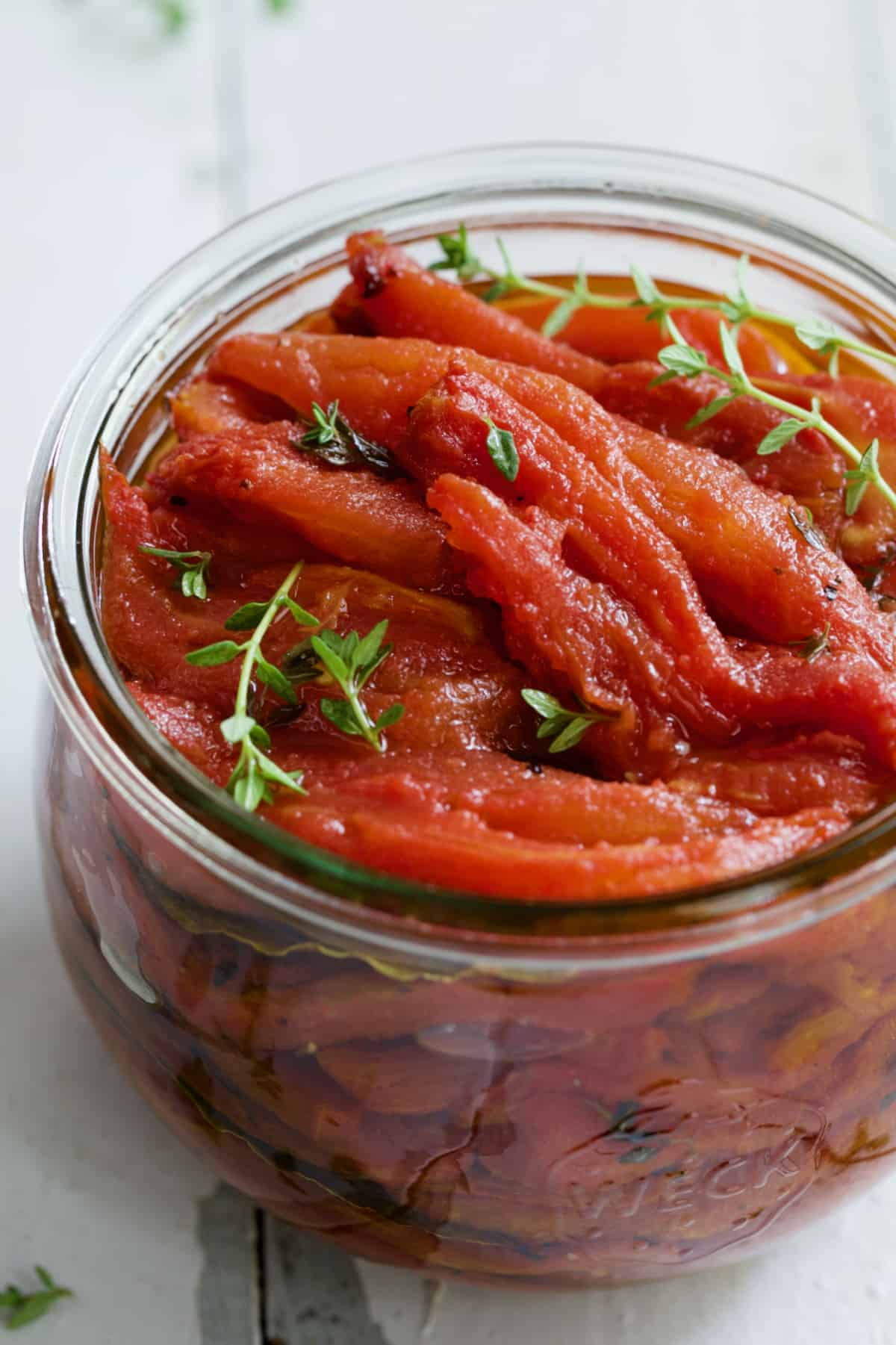 Tomato Confit in glass jar with thyme sprigs.