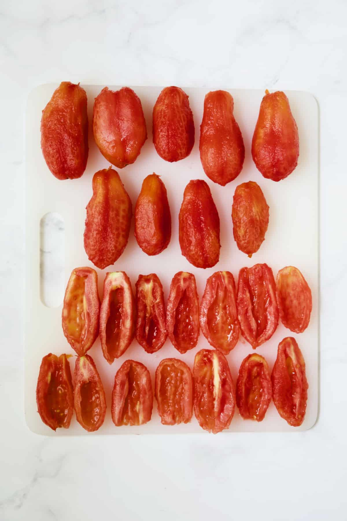 Nine whole skinned tomatoes and 14 peeled, halved and seeded tomatoes on white cutting board.
