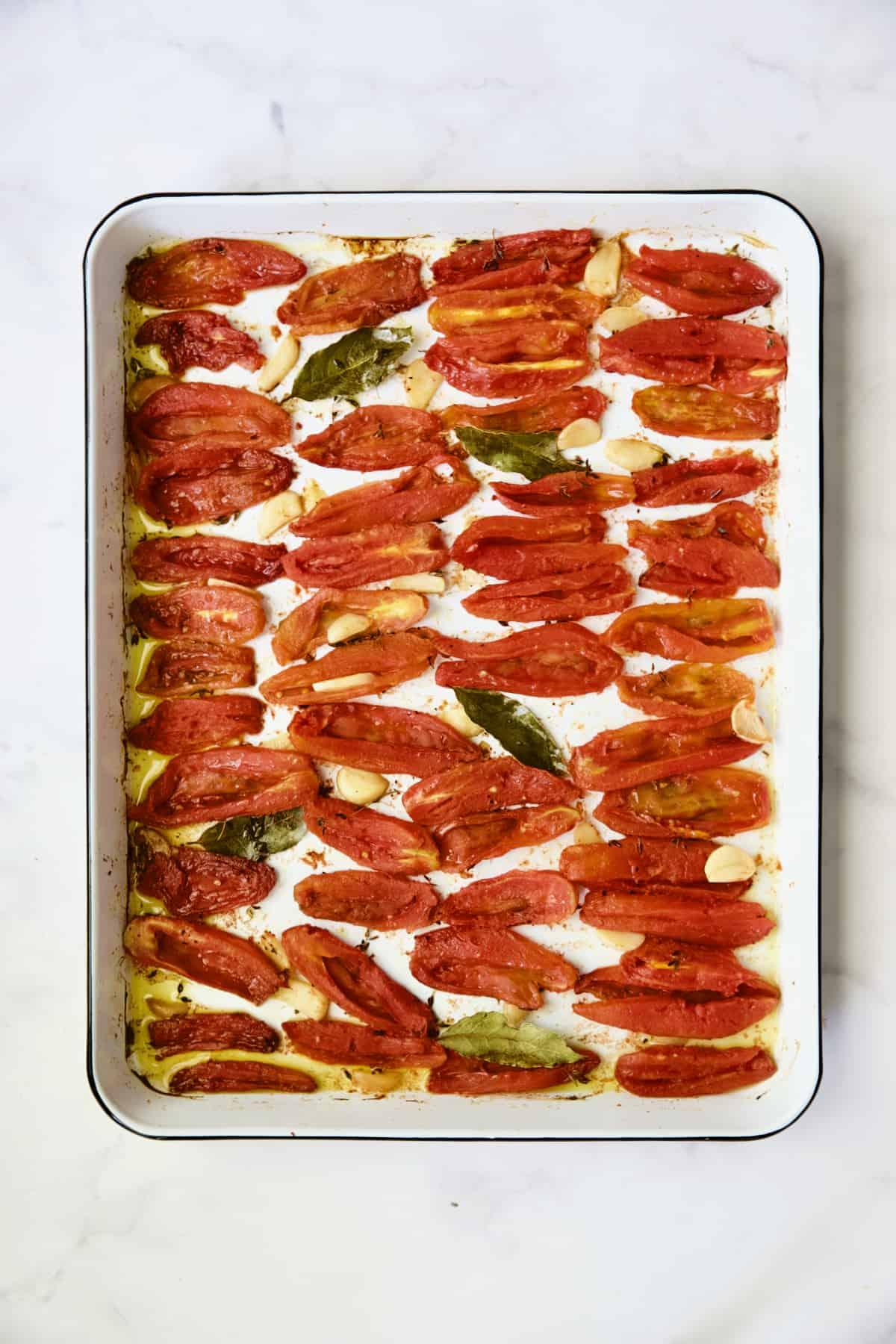 Confit tomatoes on white enameled baking sheet.