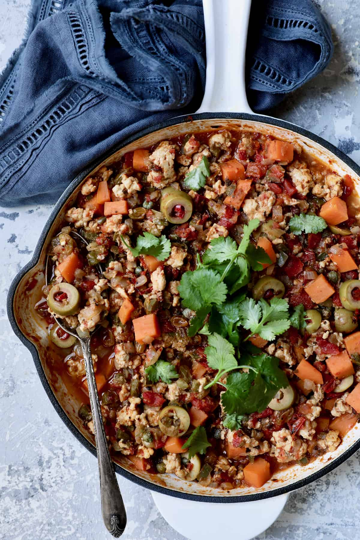 Cuban-Style Turkey Picadillo with Sweet Potatoes in white skillet with serving spoon garnished with fresh cilantro.