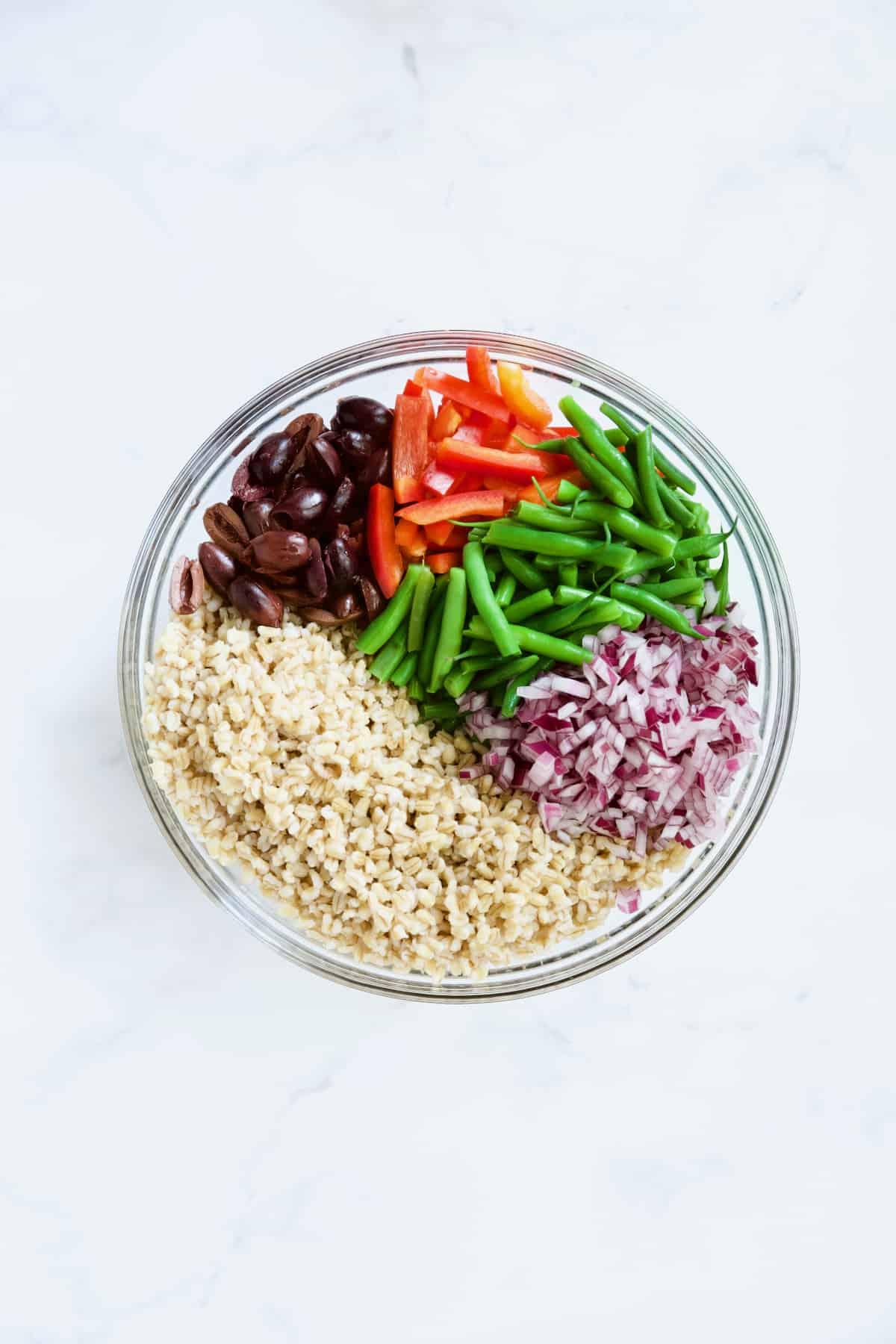 Ingredients for Mediterranean Barley Salad in glass bowl not yet stirred together.